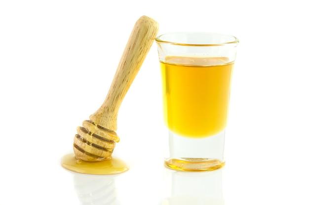Miele con mestolo di legno isolato