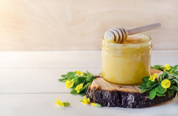 Miele con il fiore giallo dell'acacia su fondo di legno