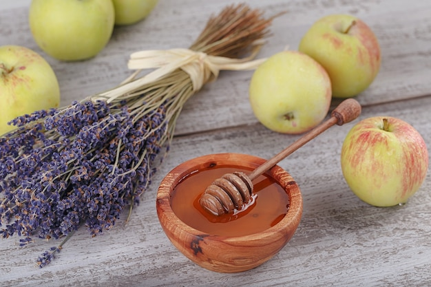 Miele in ciotola di legno con mestolo di miele, mele verdi e fiori di lavanda su sfondo bianco in legno vintage