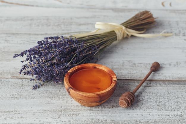 Miele in ciotola di legno con mestolo di miele e fiori di lavanda su fondo di legno vintage bianco Foto Premium