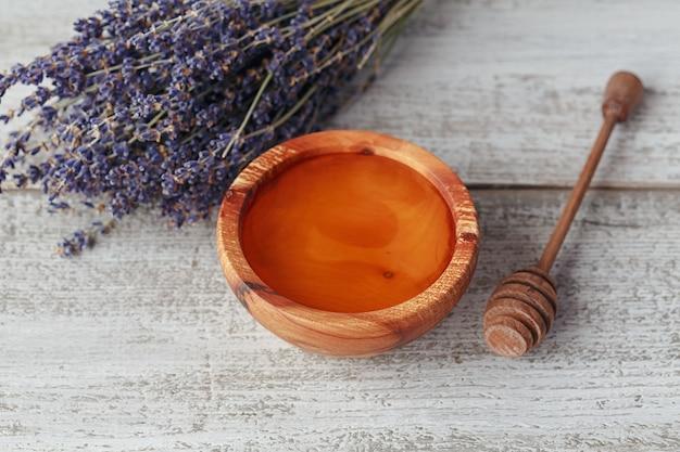 Miele in ciotola di legno con mestolo di miele e fiori di lavanda su fondo di legno vintage bianco