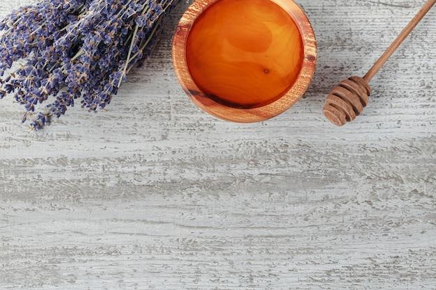 Miele in ciotola di legno con mestolo di miele e fiori di lavanda su sfondo bianco in legno vintage