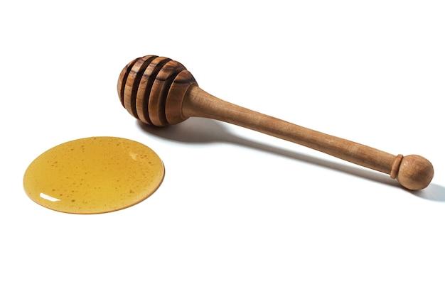 Miele e mestolo di legno isolato su superficie bianca