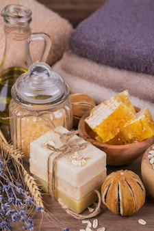 Favo, olio cosmetico, sale marino, avena e sapone fatto a mano con miele su fondo di legno rustico. ingredienti naturali per maschere o scrub fatti in casa per viso e corpo. cura della pelle sana. concetto di stazione termale.