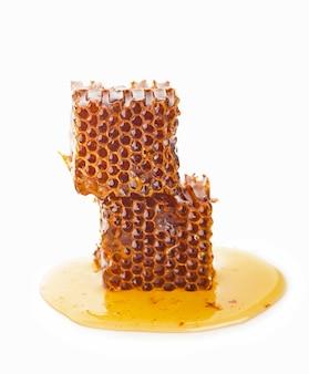 Pezzo a nido d'ape. fetta di miele isolato su superficie bianca. elemento di design del pacchetto