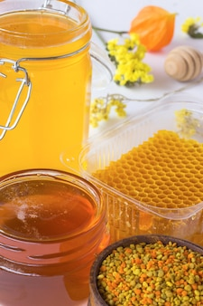 Favo, polline e vasetti di miele. mestolo miele e fiori