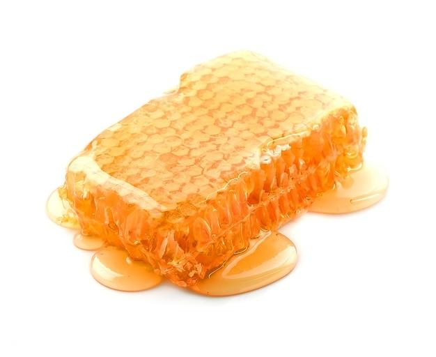 Favo con miele liquido isolato.