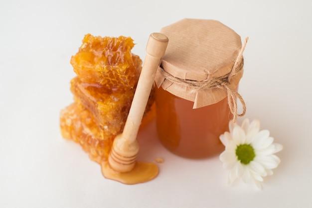 Favi d'ape, vaso di miele, fiore e dipper