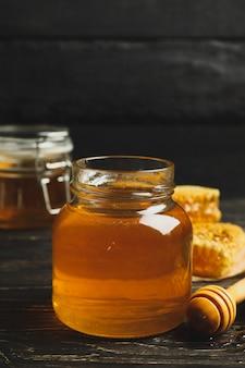 Favi, vaso con miele e mestolo su fondo di legno