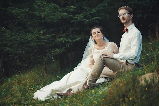 Luna di miele. la sposa e lo sposo seduti sull'erba. estate.