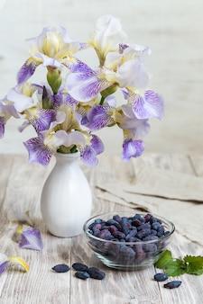 Vaso di caprifoglio sul tavolo di legno con frutti di bosco