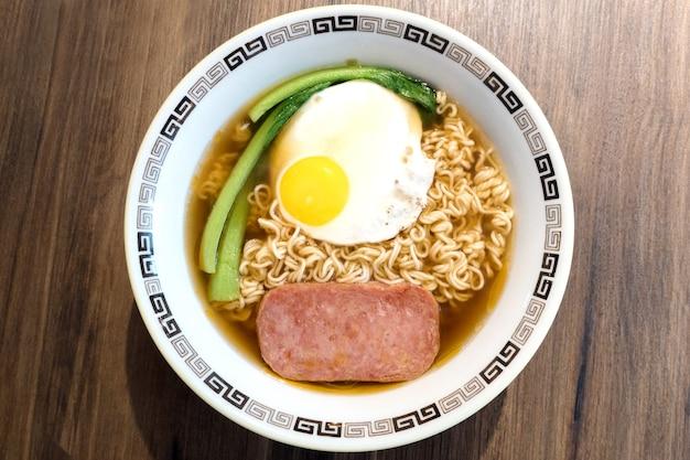 Colazione di hong kong, uova fritte al lato del sole e carne per pranzo su noodle istantanei