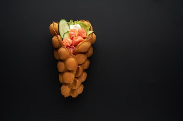 Hong kong o bubble waffle con salmone fresco e salsa su bakground scuro. concetto di cibo di strada