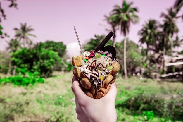 Dessert di waffle di hong kong in mano dolci con sciroppo di biscotti gelato e dolci