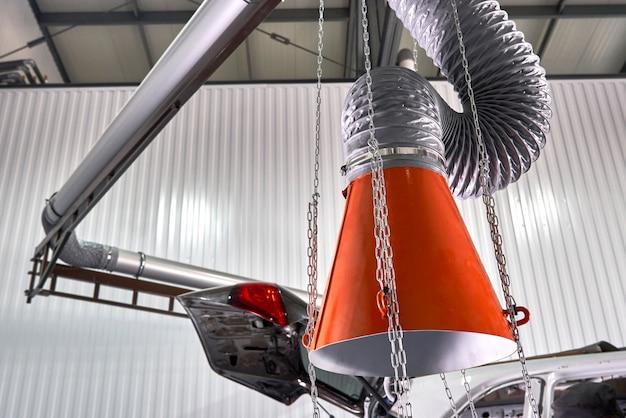 Cappuccio di un estrattore d'aria industriale nell'officina riparazioni automatica Foto Premium
