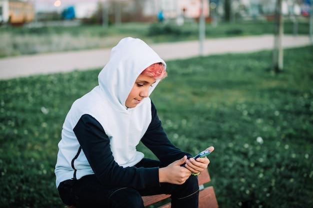 Adolescente incappucciato che esamina il cellulare in un parco
