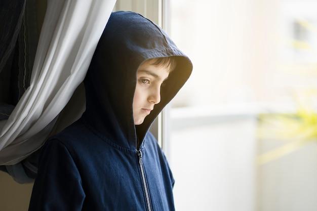 Felpa con cappuccio bambino appoggiato alla finestra vietato uscire a giocare durante il periodo di chiusura durante la chiusura