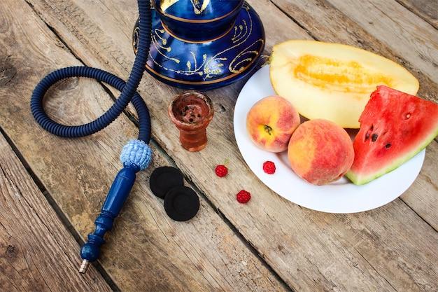 Narghilè, frutta, bacche sulla vecchia superficie di legno.