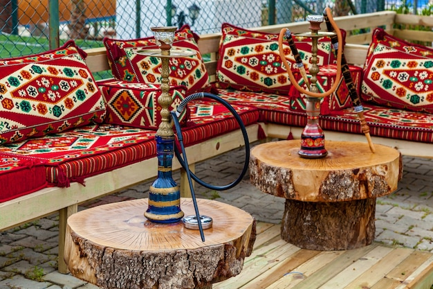 Narghilè su un tavolo di legno e cuscini multicolori luminosi sul divano, narghilè in turchia