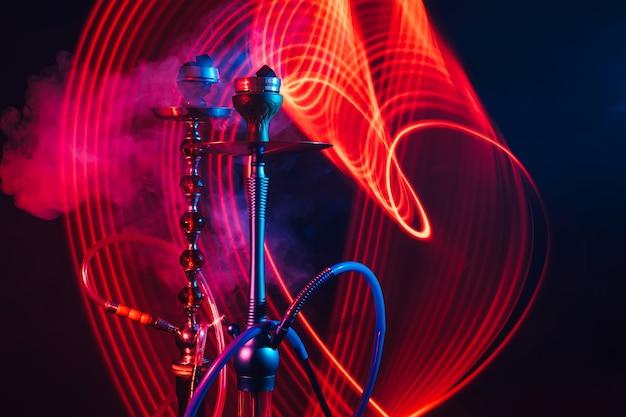 Narghilè con carbone shisha caldo con illuminazione al neon rossa e blu su sfondo scuro