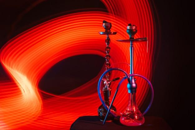 Narghilè con carboncini shisha caldi in ciotole sul tavolo su uno sfondo scuro con bagliore al neon rosso