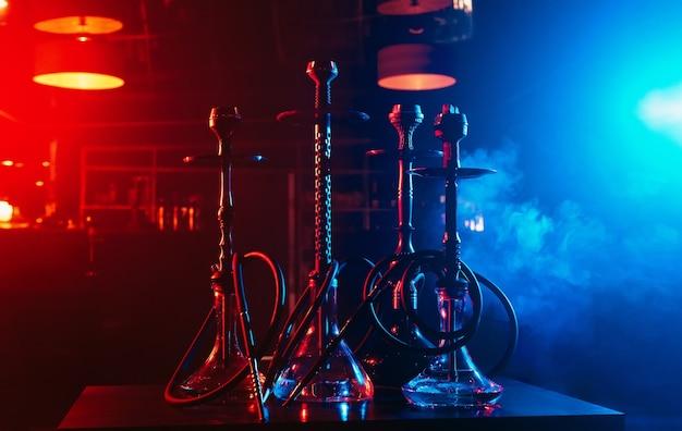 Narghilè con narghilè ciotole e carboni sullo sfondo del fumo nel ristorante per il relax con l'uso del tabacco