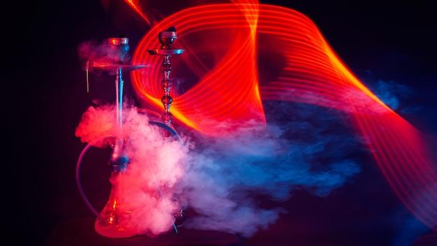 Narghilè con carboni shisha in ciotole sul tavolo con luci al neon rosse e blu
