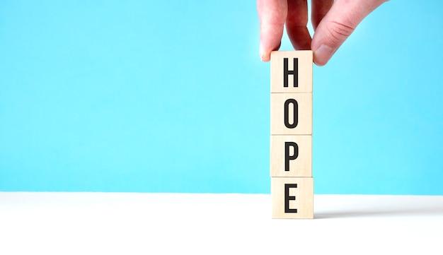 Cubi di legno del nuovo anno speranza sul fondo della tavola blu con lo spazio della copia per testo. obiettivi aziendali, missione, risoluzione, nuovo anno nuovo concetto