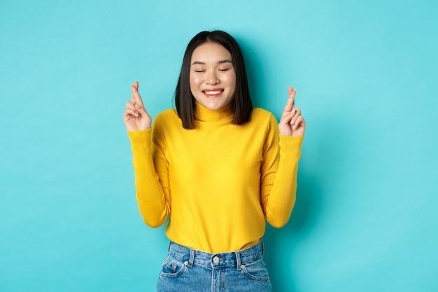 Speranzosa donna asiatica che sogna, incrocia le dita per buona fortuna e esprime desideri, prega o supplica, sorride con gli occhi chiusi, in piedi su sfondo blu.