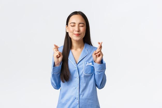 Speranzosa ragazza asiatica felice in pigiama blu che sorride con gli occhi chiusi, incrocia le dita in bocca al lupo, esprime desideri, prega o supplica per il sogno che si avvera, anticipando notizie positive sul muro bianco
