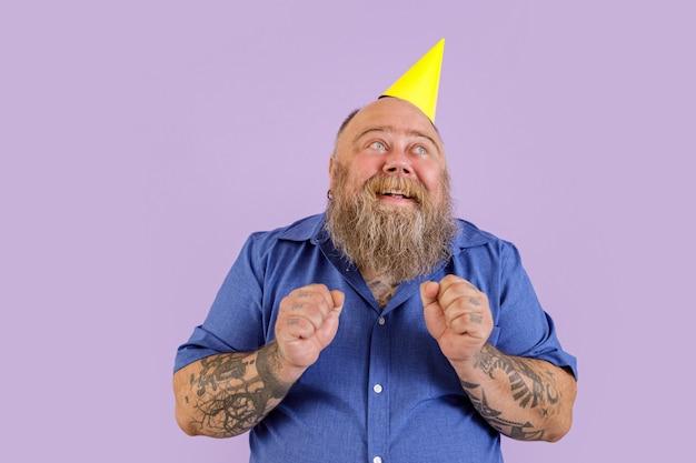 Speranzoso maschio barbuto di mezza età con sovrappeso in cappello da festa tiene i pugni in piedi su sfondo viola in studio