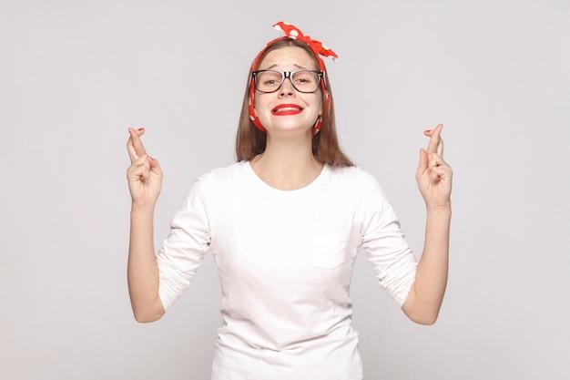 Speranzoso ritratto di bella giovane donna emotiva in maglietta bianca con occhiali, labbra rosse e fascia per la testa che guarda l'obbiettivo con il dito incrociato. tiro al coperto, isolato su sfondo grigio chiaro.