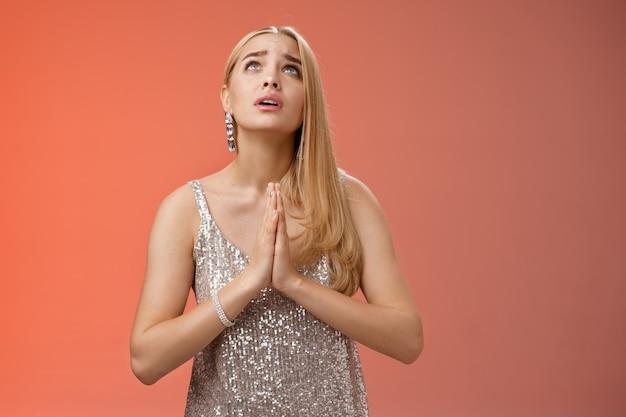 Hopeful preoccupato preoccupato fedele donna bionda in abito d'argento pregando dio parlante che desidera la famiglia va bene premere i palmi insieme supplicando nervosamente implorando, in piedi vestito elegante sfondo rosso.