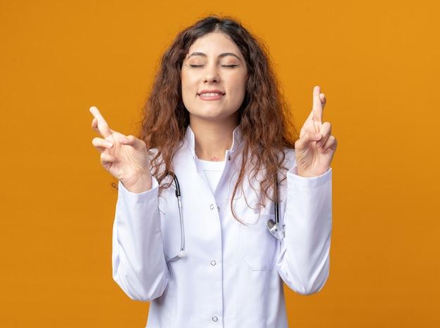Speranzosa giovane dottoressa che indossa una tunica medica e uno stetoscopio che fa un gesto di buona fortuna con gli occhi chiusi isolati sulla parete arancione