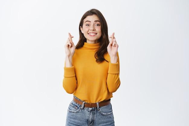 Speranzosa giovane donna incrocia le dita e aspetta buone notizie, anticipando che accada qualcosa, esprimendo desideri o pregando, in piedi contro il muro bianco