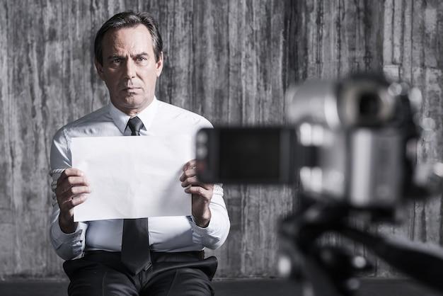 Ostaggio senza speranza. uomo d'affari frustrato catturato da un criminale seduto di fronte a un muro sporco e in possesso di carta mentre la videocamera la riprende in primo piano