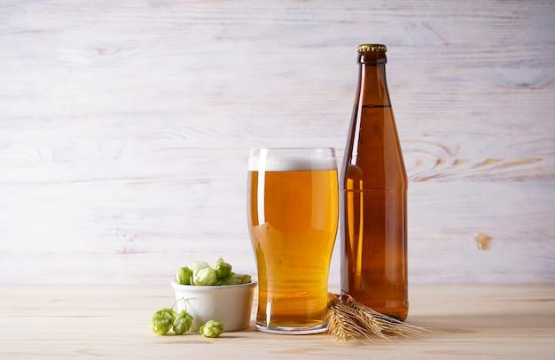 Luppolo e birra chiara su uno spazio di legno