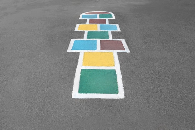 Gioco della campana che viene disegnato con una vernice colorata sull'asfalto visto dall'alto
