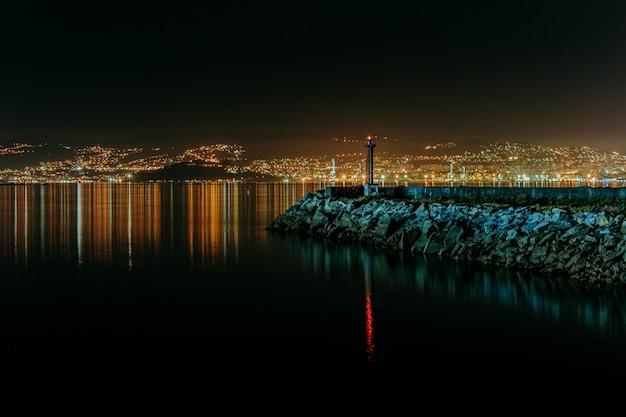 Un colpo colorato orizzontale del faro durante la notte con lo skyline della città