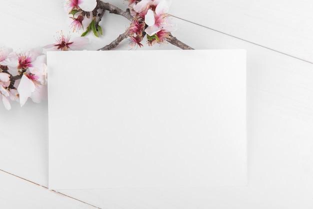 Mockup di carta vuota orizzontale con ramo di mandorlo in fiore