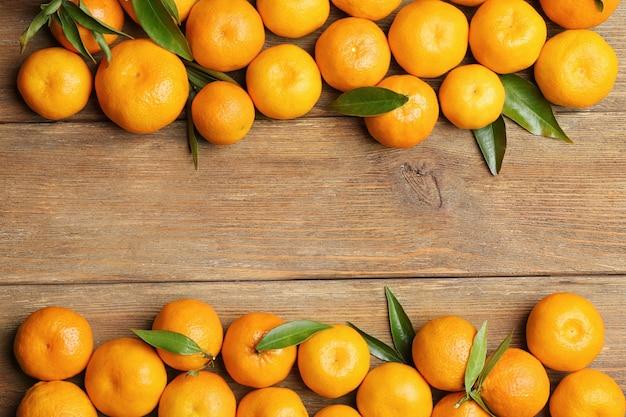 Cornice orizzontale fatta di mandarini su fondo in legno