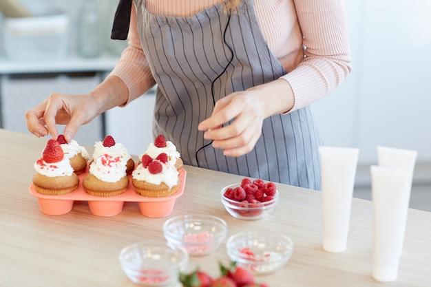 Colpo orizzontale alto angolo di irriconoscibile giovane donna che decora cupcakes fatti in casa con frutti di bosco freschi