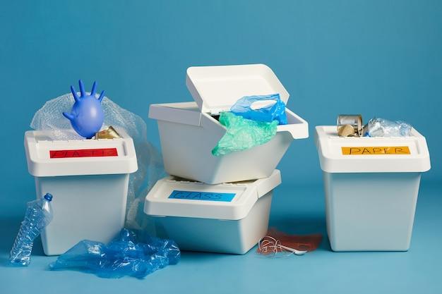 L'immagine orizzontale di bidoni della spazzatura pieni per rifiuti di plastica e carta in fila, concetto di smistamento e riciclaggio