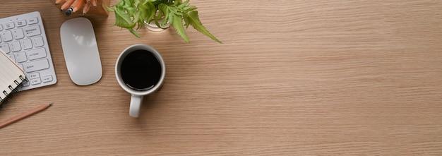 Immagine orizzontale della scrivania da ufficio con tazza di caffè, pianta, taccuino e copia spazio su sfondo di legno.