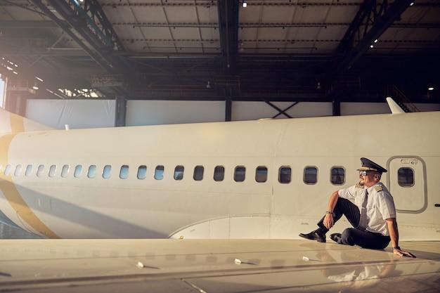 Immagine orizzontale del pilota premuroso seduto sull'aereo e guardando la distanza isolata sullo sfondo della fusoliera