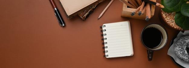 Immagine orizzontale del posto di lavoro vintage con tazza di caffè, taccuino, cancelleria e copia spazio in pelle marrone.