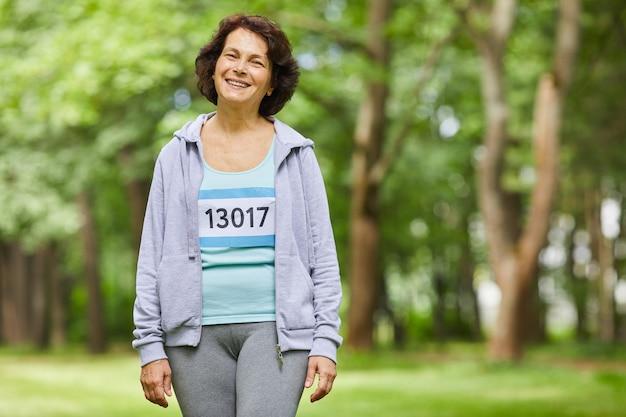 Colpo medio orizzontale della donna invecchiata allegra con capelli ondulati marroni che indossa attrezzatura sportiva che sorride alla macchina fotografica