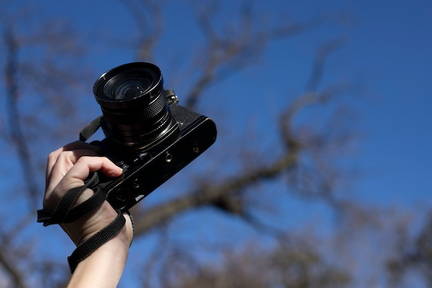 Foto orizzontale della mano che tiene la fotocamera retrò con sfondo blu all'esterno