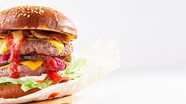 Foto orizzontale di un gustoso hamburger con carne di manzo, formaggio giallo, funghi, sottaceti, cipolla e ketchup isolato su uno sfondo bianco. spazio per un testo. messa a fuoco selettiva.
