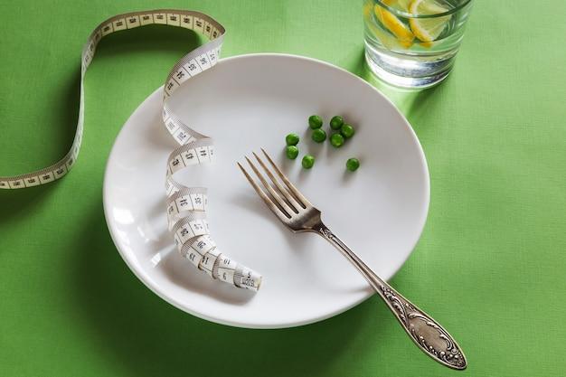 Foto orizzontale del piatto bianco con forchetta, centimetro, piselli